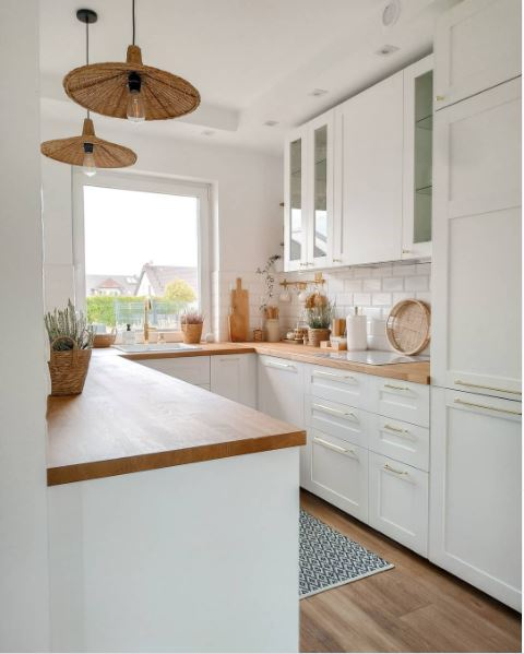 A charming kitchen in white with a large picture window and butcher block countertop