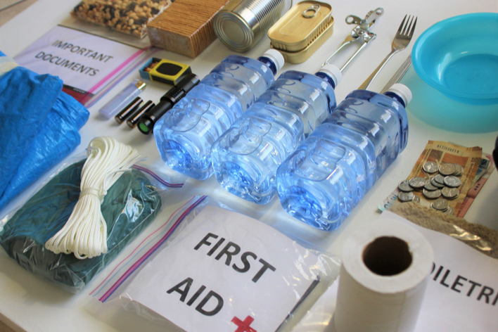 Emergency supplies to prepare your home for hurricane season that include water bottles, first aid kit, important documents, etc.