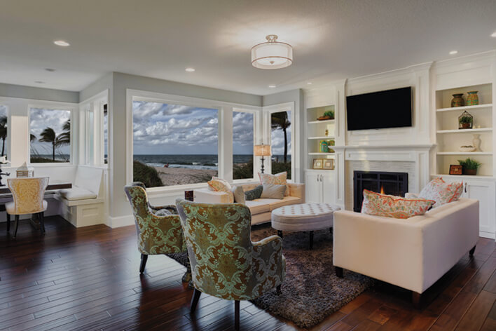 A living area in a beachfront home with large windows that a homeowner will need to prepare for hurricane season