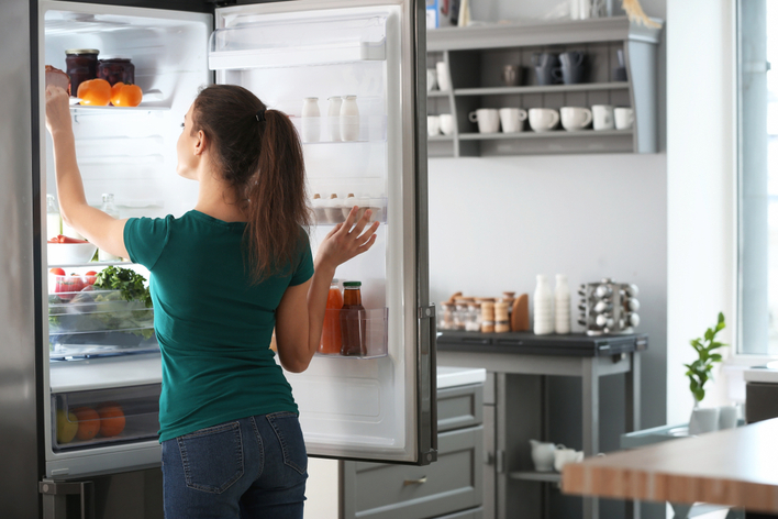 A woman preparing her home for hurricane season by lowering the temperature in her fridge