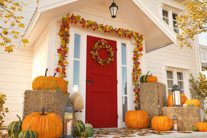 A red front door with fall décor