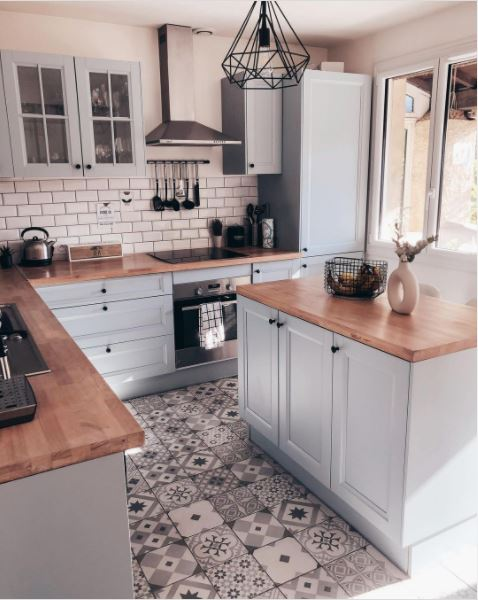 A wonderful kitchen with blue cabinets and a patterned floor