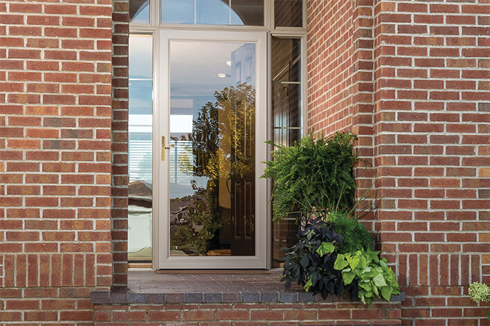 A storm door on the front of a brick home