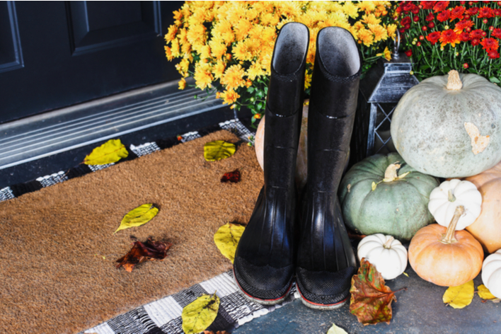 An idea for decorating a front porch for fall is rain boots and mums