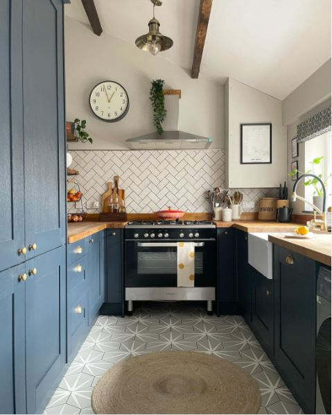 A rustic kitchen with blue cabinets and grey walls