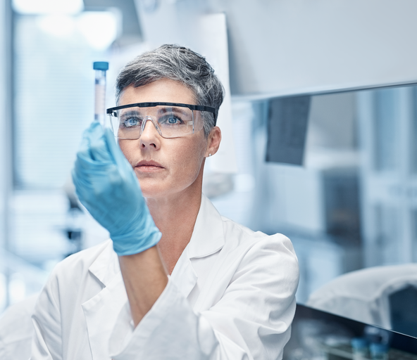 Woman works in a pharmaceuticals labor under controlled environments