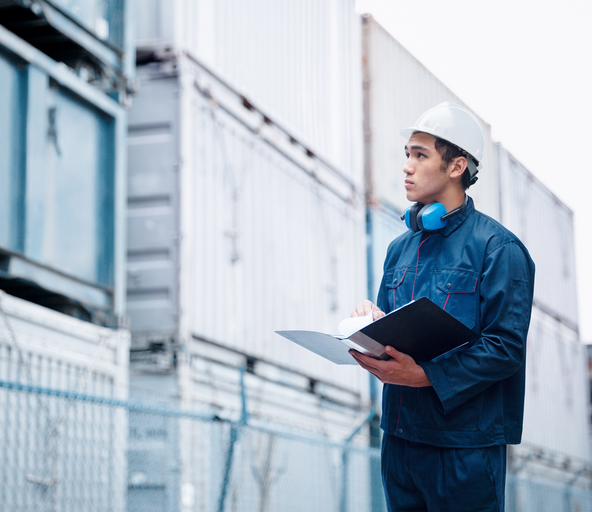 Man standing in front of containers and planning their shipping