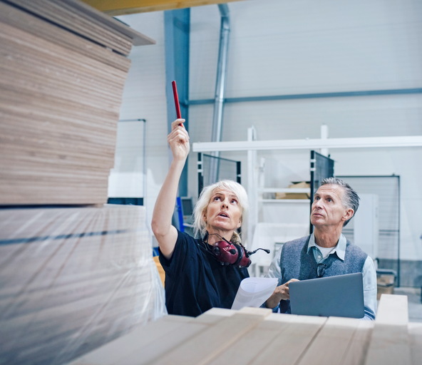 Two people in a warehouse for wood and furniture