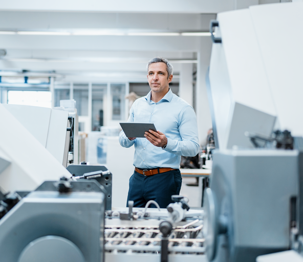Software expert standing next to a conveyor system with a tablet