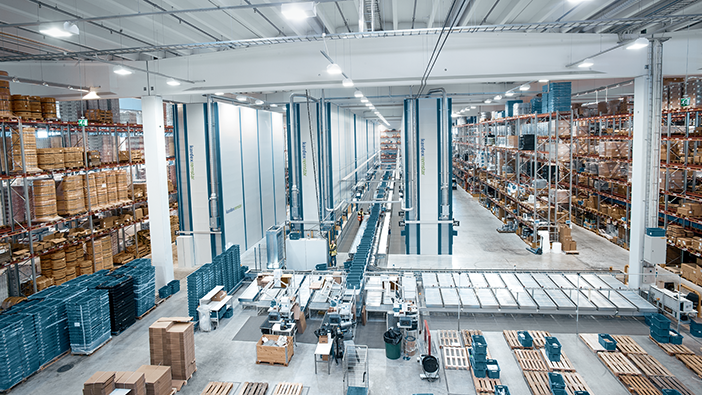 Distribution center with storage in static shelves, on pallets and in vertical lift systems