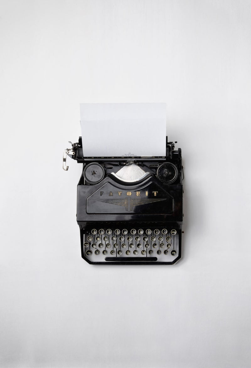 A black Favorit typewriter with 3 lines of text on a paper