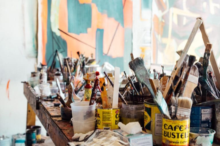 Many paintbrushes on a table soaking in cups and coffee cans