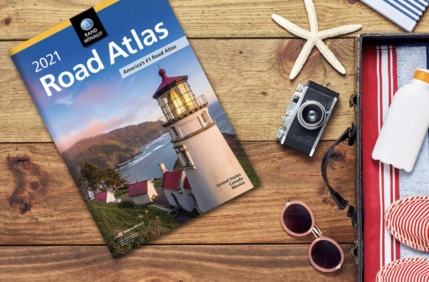 Rand McNally Road Atlas on top of wooden table along with sunglasses, a camera, sunscreen and a starfish