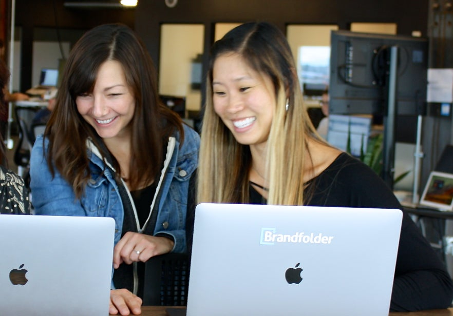 Two smiling women with Brandfolder laptops look at one of the laptop screens.