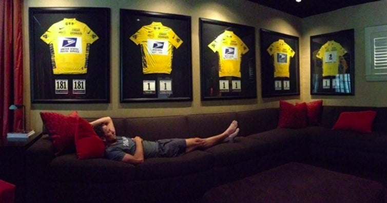 Lance Armstrong on his couch surrounded by his Tour de France jerseys