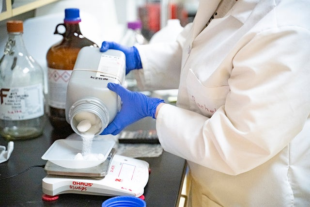 scientist pouring out supplement
