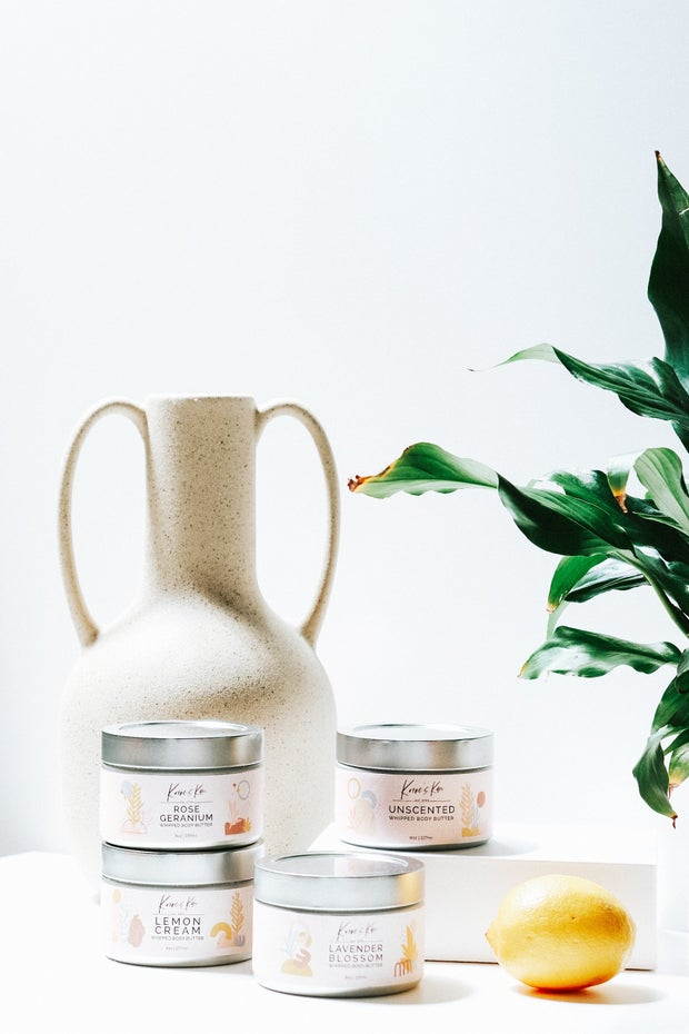 Body butters and lip balms are displayed against a white backdrop with some plants and other decor