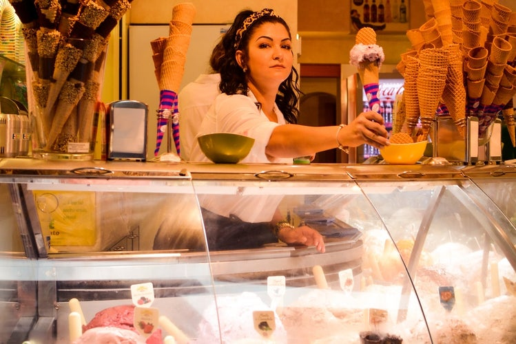 Girl working behind counter at ice cream shop