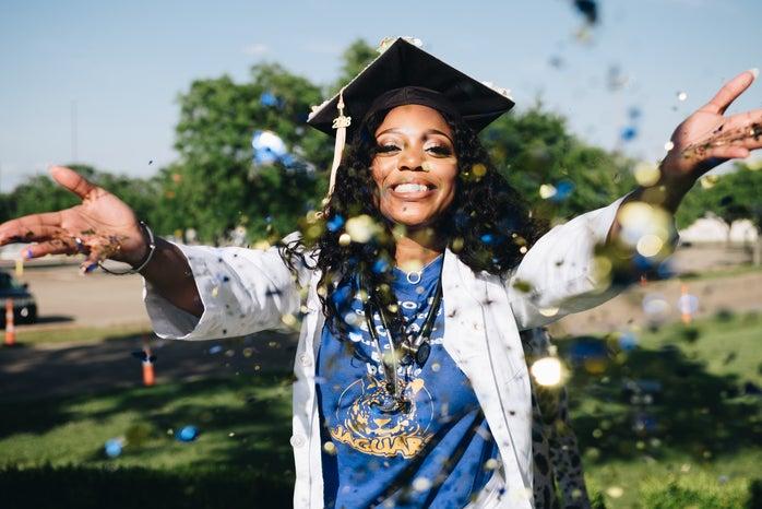 woman graduating throwing confetti