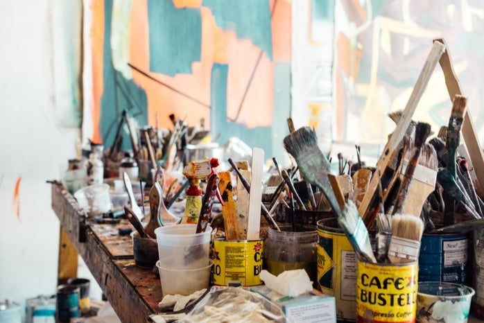 it is an image of paints and paint brushes on a table