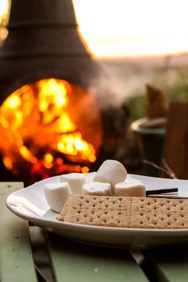 s'mores ingredients on white plate in front of fire