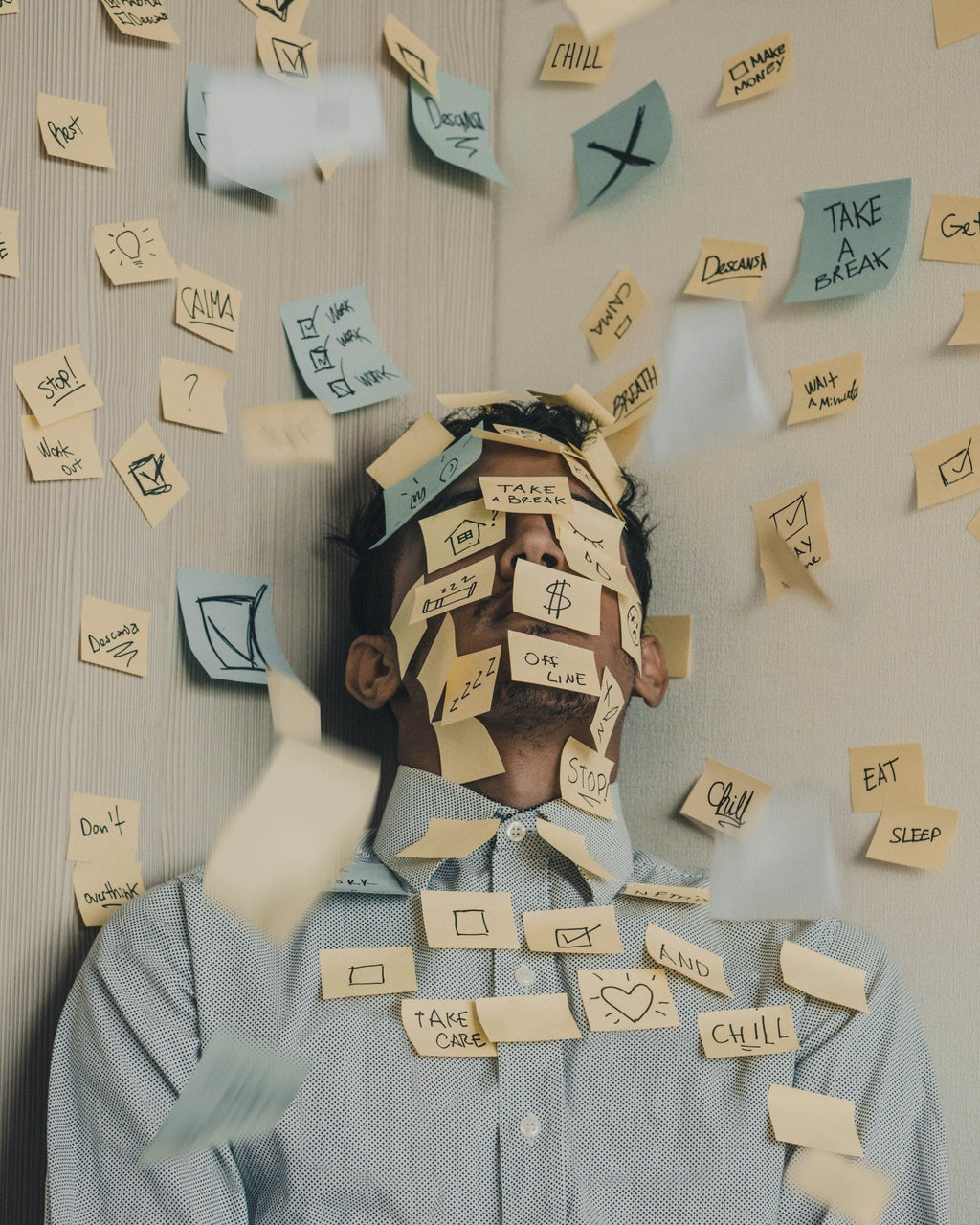 man laying down covered in sticky notes