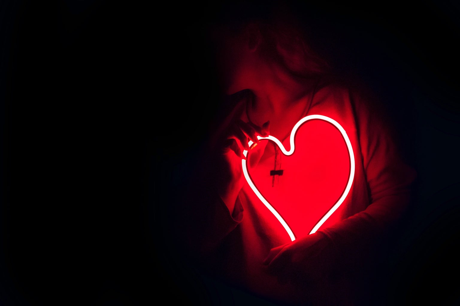 woman holding a neon red heart