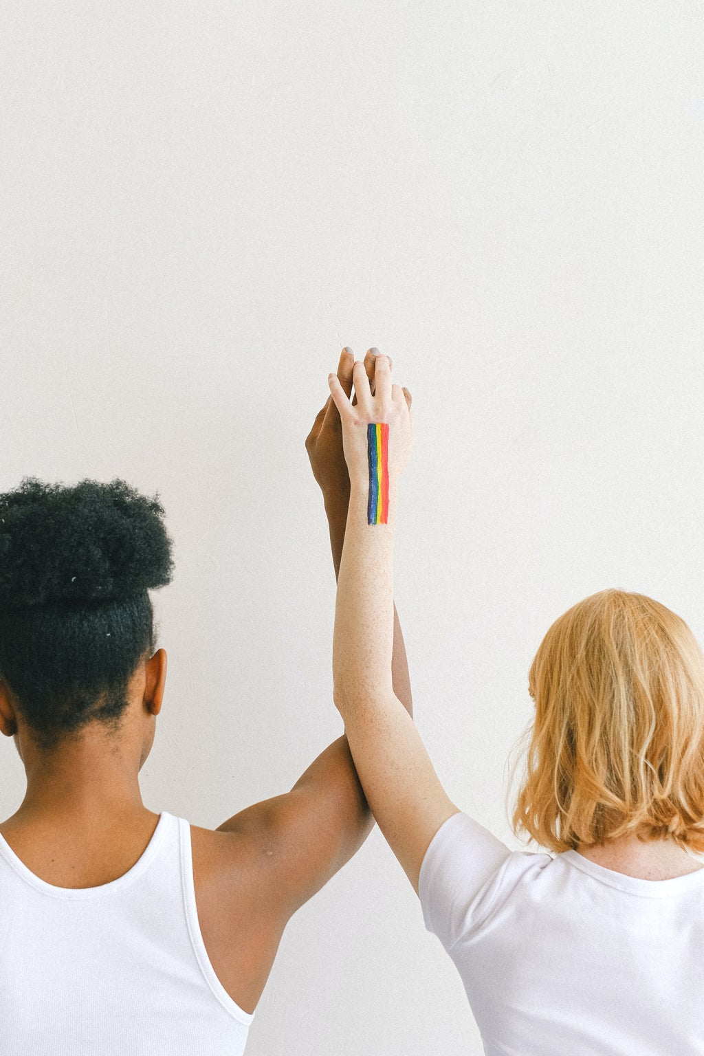 Two women hold hands with a rainbow painted on them