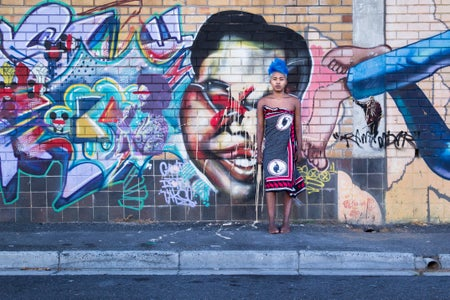 African girl wearing tradition clothing in front of a wall filled with graffiti, a common way Africans express their creativity.