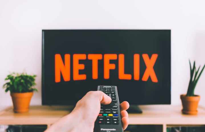 person holding a remote control pointed at TV streaming netflix