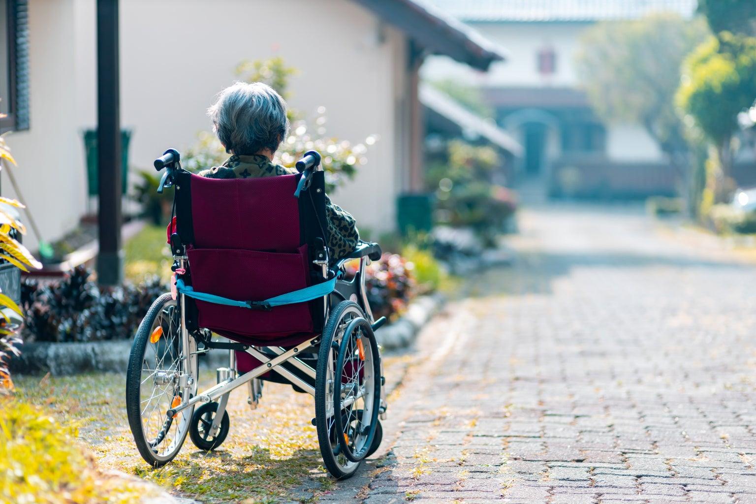 Woman in wheelchair in front of neighborhood