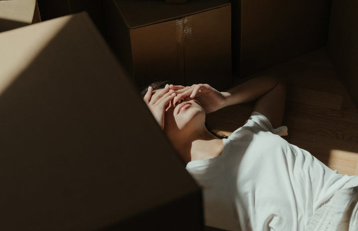 sad young woman laying by boxes
