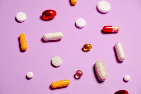 Vitamins laying on a pink background