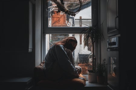 Woman wearing mask sitting by the window