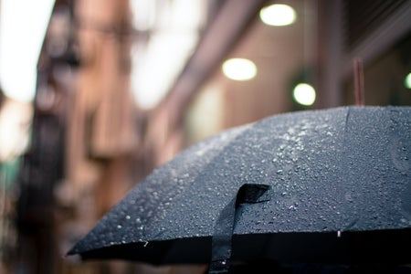 raindrops on a black umbrella with a blurred background