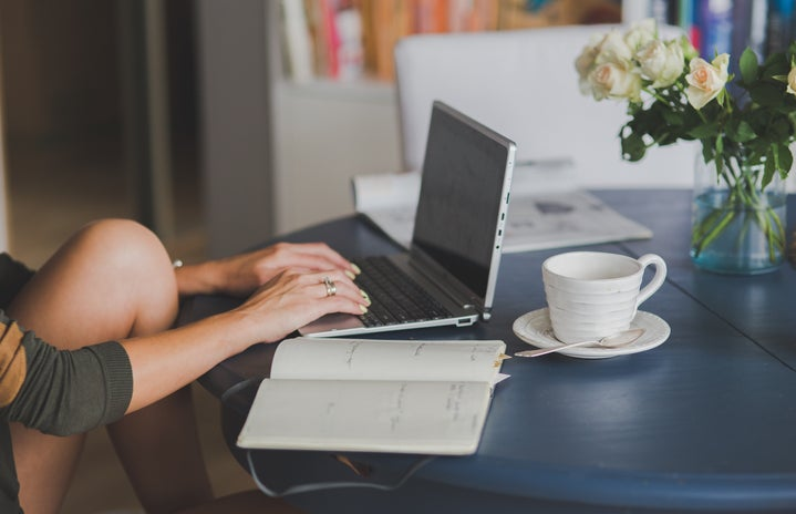 A woman works on a computer, and the table has a coffee cup and open notebook.