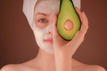 woman with white face mask holding an avocado