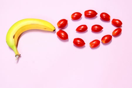 Banana and cherry tomatoes on pink background