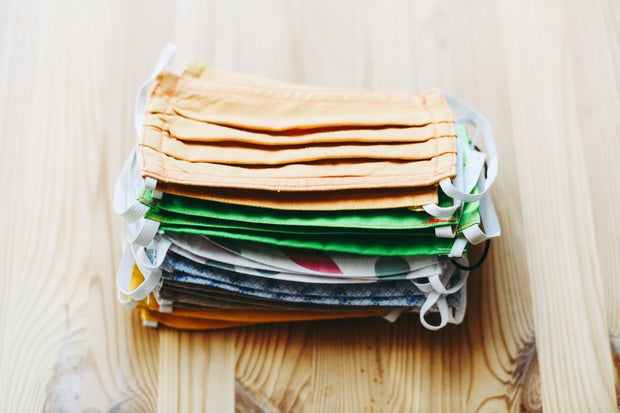 Stack of cotton face masks on wooden table.