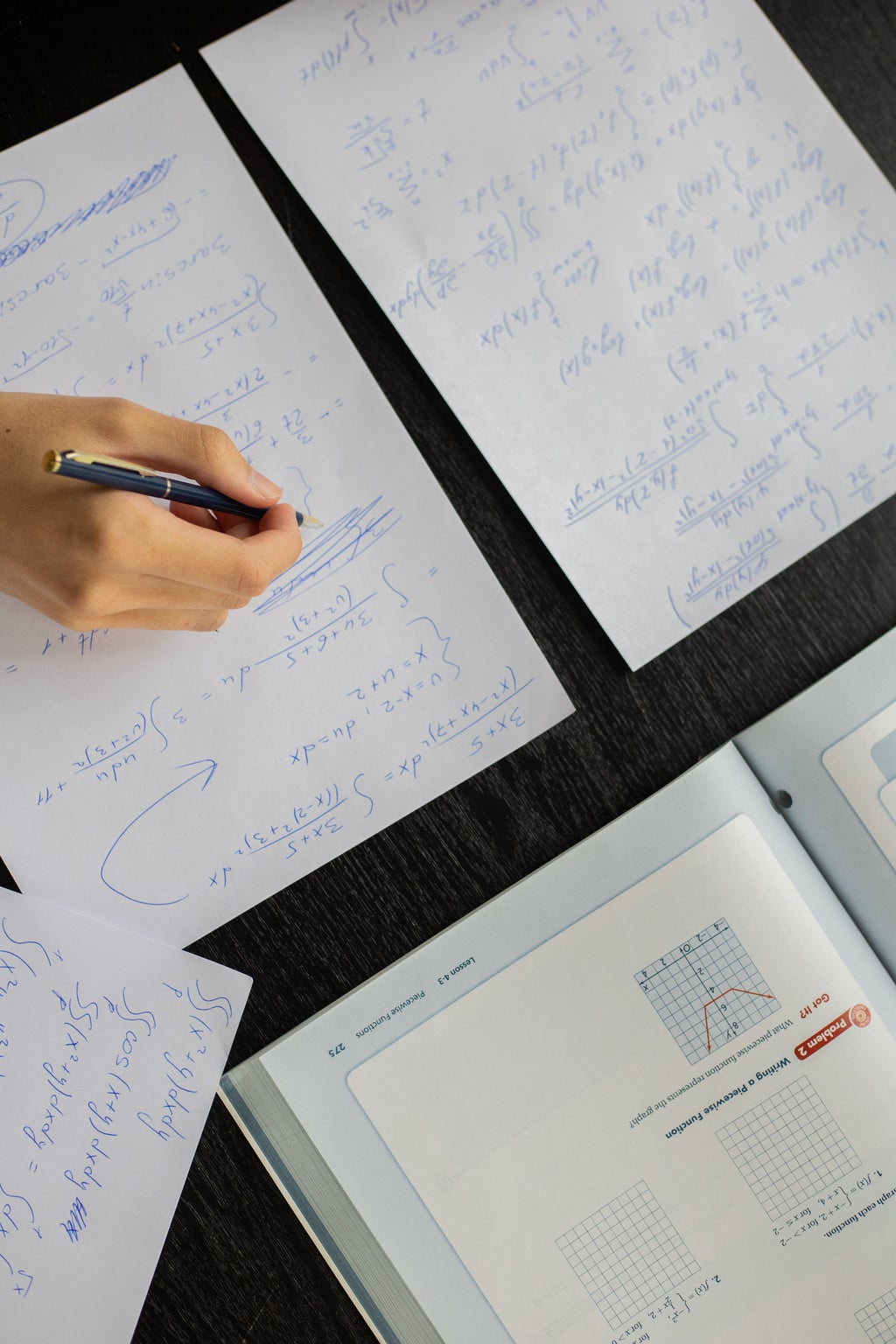 person writing notes while reading a textbook