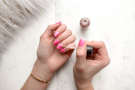 woman painting nails with pink polish