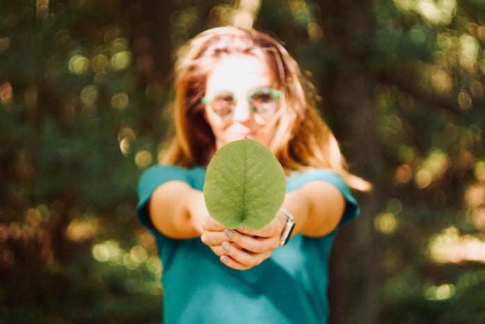 Woman holding leaf.