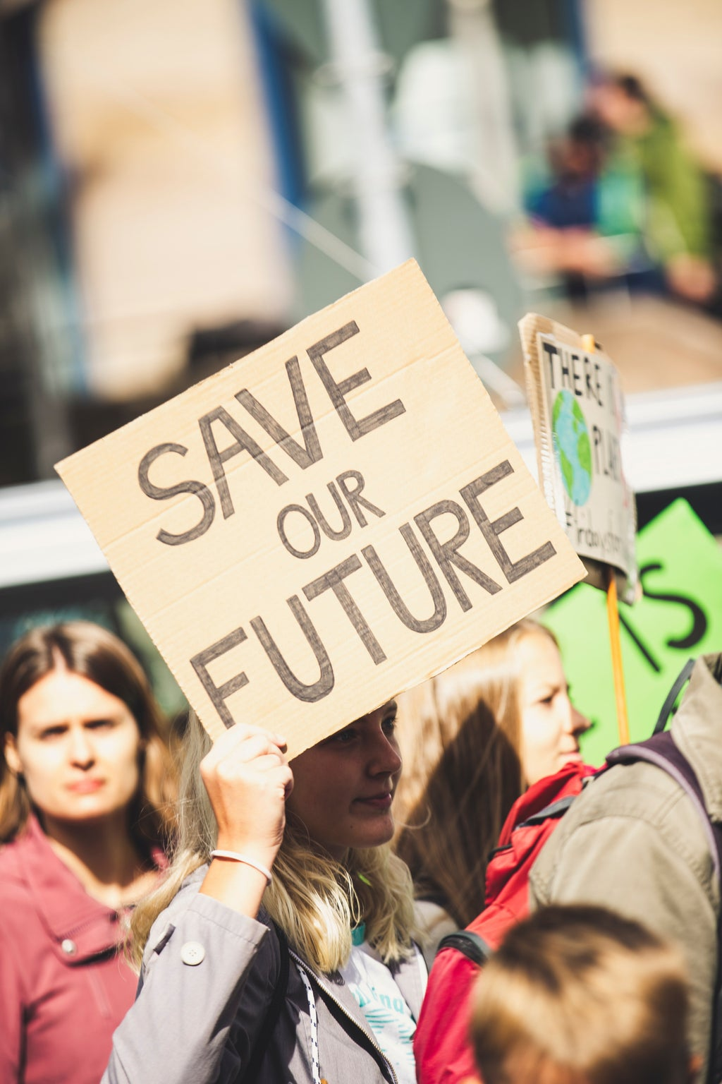 """Woman holding \""""Save Our Future\"""" sign"""