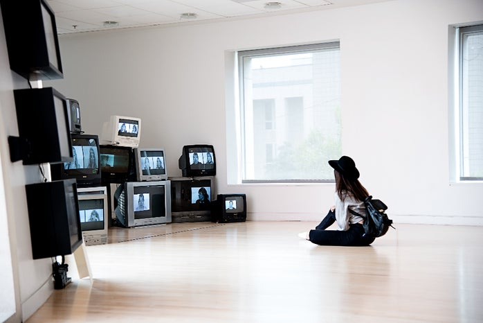 Girl sitting on floor, looking at multiple televisions