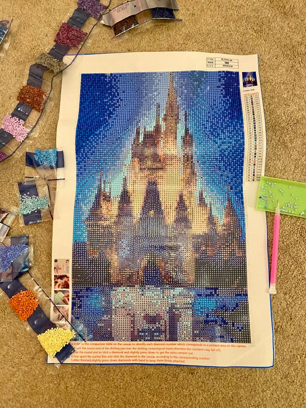 Disney castle incomplete diamond painting surrounded by bedazzle packets.