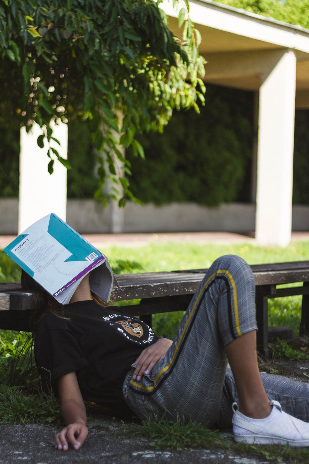 person sitting against bench with a book covering their face