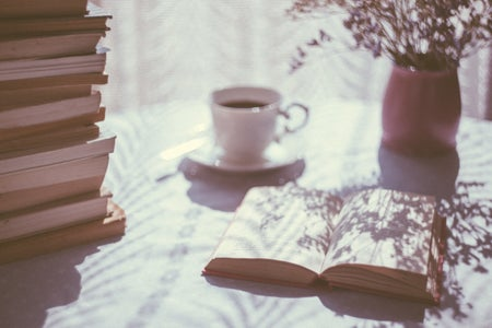 open book next to teacups, plant, and stack of books