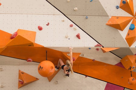 her campus western, woman bouldering on indoor wall