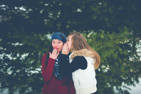 image of two women whispering
