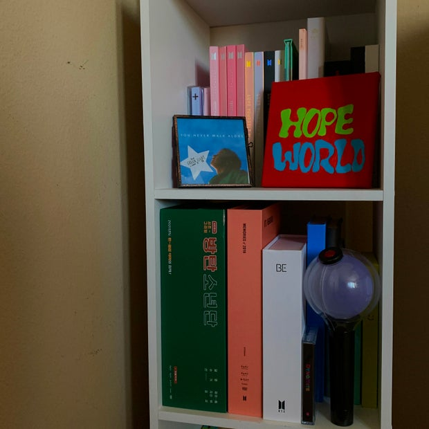BTS/K-Pop albums and lightstick on a shelve.